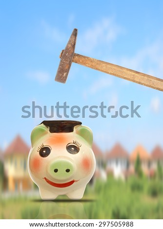 Hand with hammer about to smash piggy bank to get buy house - stock photo