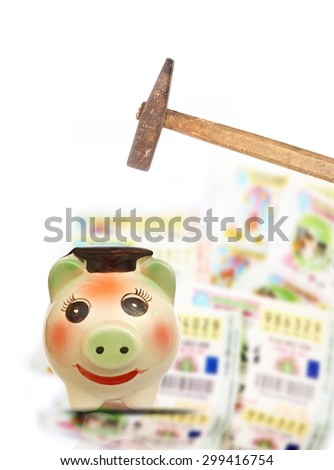 Hand with hammer about to smash piggy bank to get buy Thai lottery tickets - stock photo