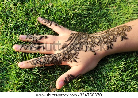 Hand with Henna Design on Green Grass