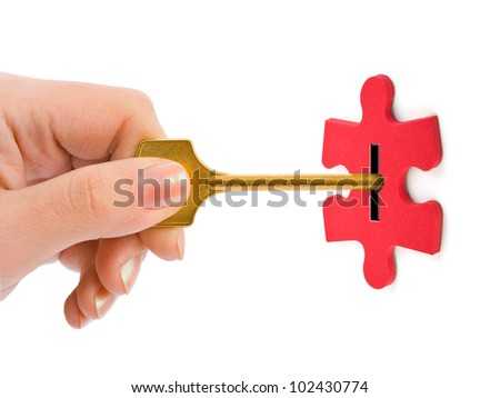 Hand with key and puzzle isolated on white background - stock photo