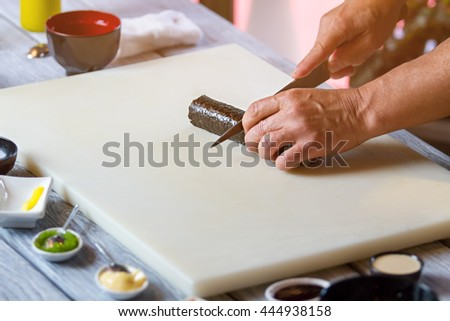 Hand with knife cuts sushi. Sushi roll on cooking board. Traditional recipe of hosomaki rolls. Japanese chef prepares food.
