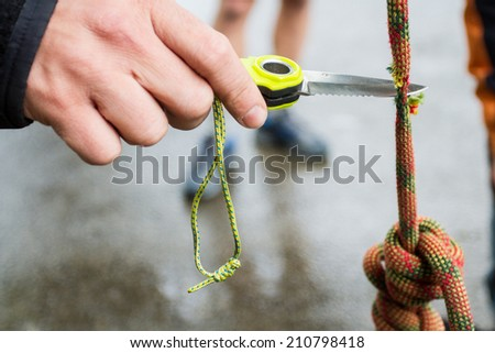 Hand with knife cutting the rope - stock photo
