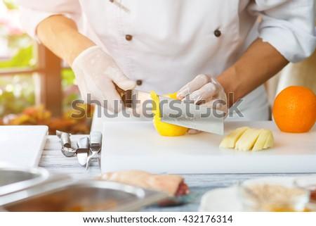 Hand with knife peels lemon. Lemon on white cooking board. Chef prepares healthy breakfast. Juicy lemon and orange. - stock photo
