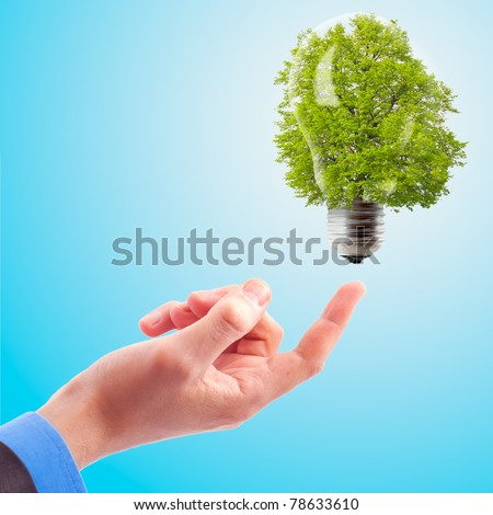 Hand with lamp and tree. The concept of renewable energy
