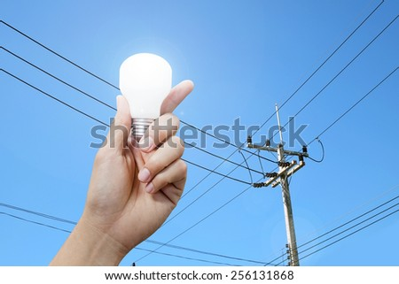 hand with light bulb, electricity pole background - stock photo