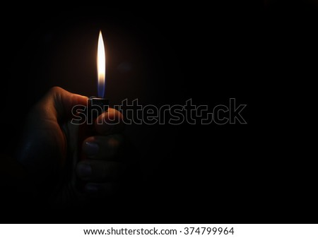 Hand with lighter igniting sparks on dark background