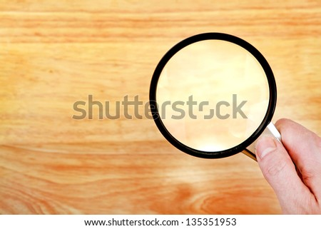 Hand With Loupe on the wooden background closeup