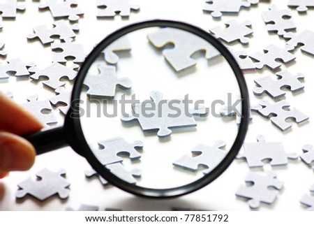 Hand with magnifying glass and puzzle isolated on white background - stock photo