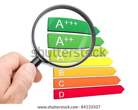 Hand with magnifying glass looking at the new A+, A++ and A+++ classes of the european energy efficiency classification - stock photo