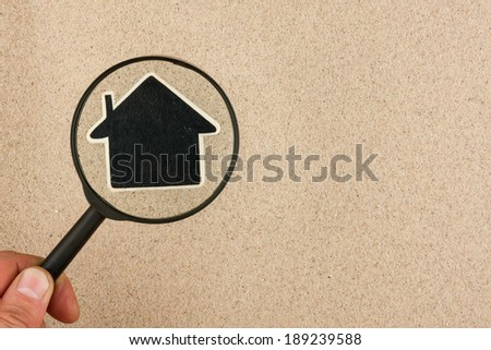 Hand with magnifying glass over the house in the sand, with space for your text - stock photo