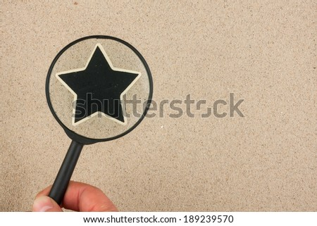 Hand with magnifying glass over the star, in the sand, with space for your text - stock photo