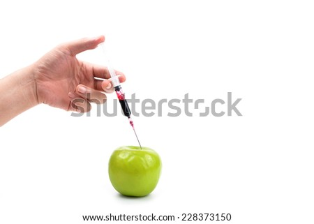 hand with medical syringe and apple isolated on white - stock photo