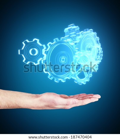 hand with metal gears and cogwheels on blue background - stock photo