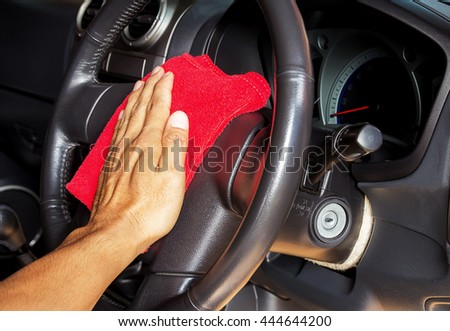 Hand with microfiber cleaning a car steering wheel auto detailing concept