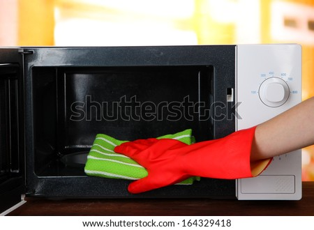 Hand with microfiber cleaning  microwave oven, on bright background - stock photo