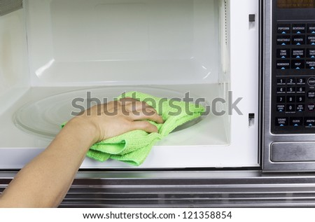 Hand with microfiber cleaning rag wiping inside of microwave oven - stock photo