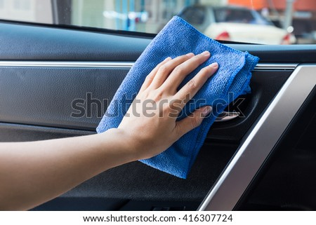 Hand with microfiber cloth cleaning Interior modern car. - stock photo