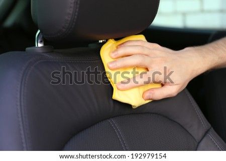 Hand with microfiber cloth polishing car - stock photo