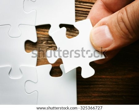Hand with missing jigsaw puzzle piece. Business concept image for completing the final puzzle piece.wooden background