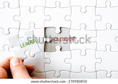 Hand with missing jigsaw puzzle piece. Word LEADER, covering  the text FOLLOWER. Business concept image for completing the final puzzle piece. - stock photo