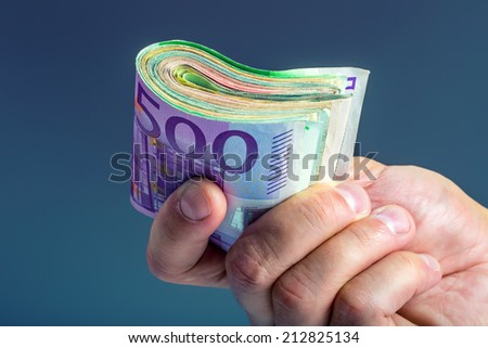 Hand with money a few hundred euros in banknotes - stock photo