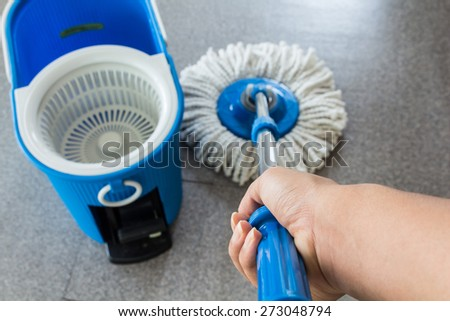 hand with mop and blue bucket cleaning a  floor from dust - hand focus - stock photo
