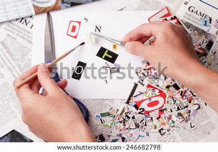 Hand with newspaper clippings alphabet with letters, numbers and symbols - stock photo