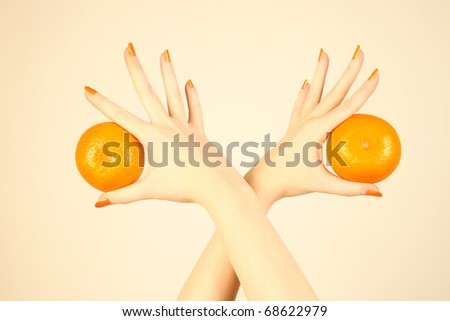 Hand with orange tangerine. Ripe mandarin in the woman's hands with orange nails. - stock photo