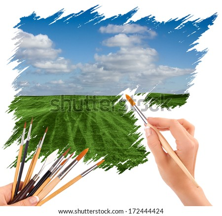 hand with paint brush painting a beautiful summer landscape with blue sky and clouds  - stock photo
