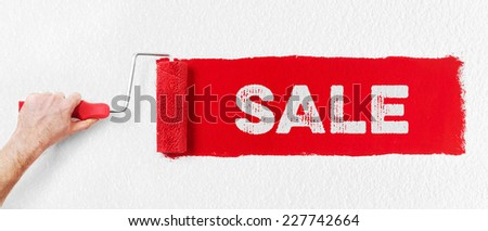 Hand with paint roller showing sale - stock photo