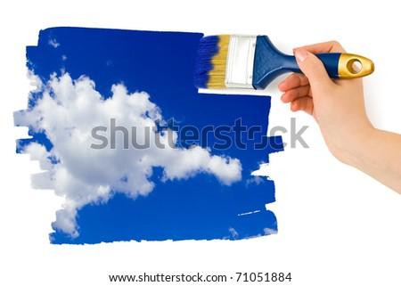 Hand with paintbrush painting sky isolated on white background - stock photo