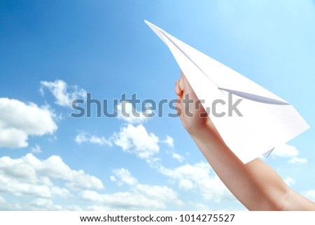 Hand with paper airplane on sky