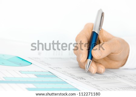 Hand with Pen Analyses Figures by Financial Charts and Graphs - stock photo