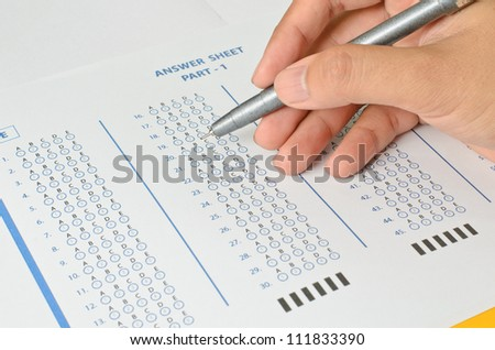 Hand with pen and Answer Sheet