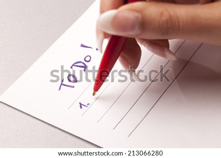 hand with pen and empty to do list - stock photo