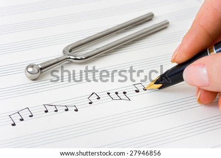 Hand with pen and music sheet, musical background