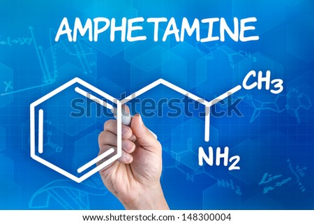 hand with pen drawing the chemical formula of amphetamine - stock photo