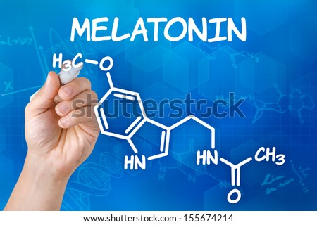 Hand with pen drawing the chemical formula of melatonin - stock photo