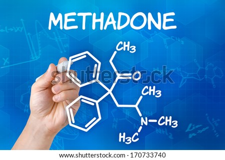 Hand with pen drawing the chemical formula of methadone - stock photo