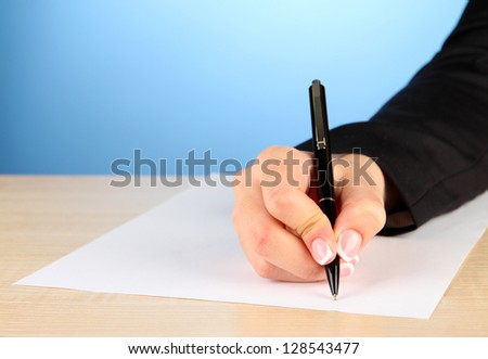 Hand with pen on white paper, on wooden  table on blue background