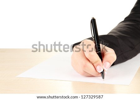 Hand with pen on white paper, on wooden  table on white background