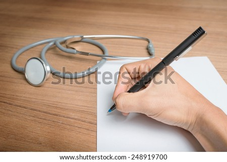 Hand with pen over blank paper form with stethoscope. - stock photo
