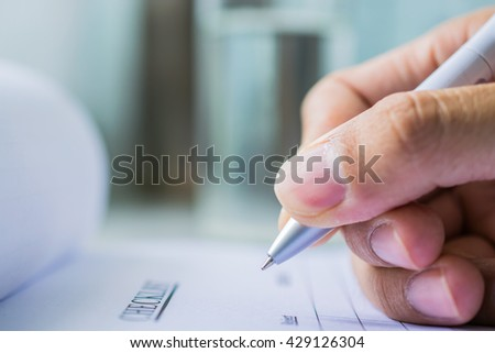 Hand with pen over checklist from on blure water glass background - stock photo