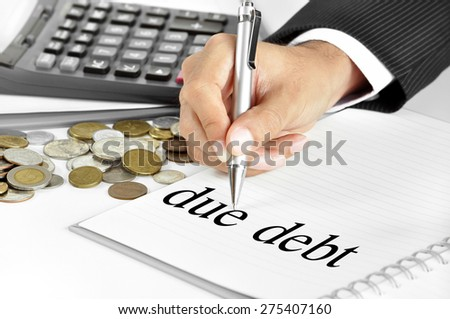 Hand with pen  pointing to due debt word on the paper - financial and investment concepts - stock photo