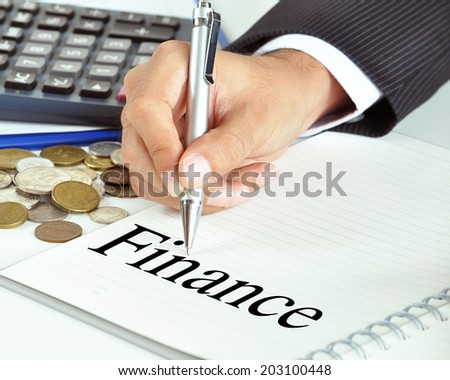 Hand with pen pointing to Finance word on the paper - business & financial concept - stock photo