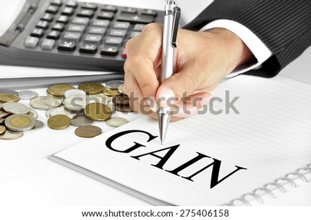 Hand with pen  pointing to GAIN word on the paper - financial and investment concepts - stock photo