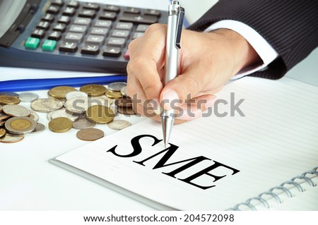 Hand with pen pointing to SME (or small and medium enterprises) sign on the paper - stock photo