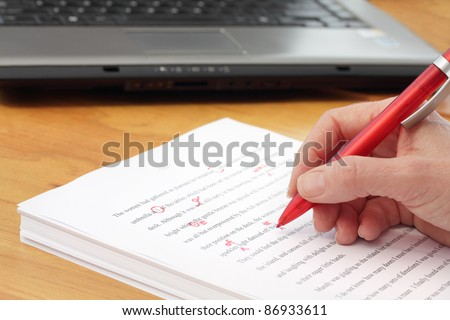 Hand with Pen Proofreading a Manuscript - undiscernable text so can be any Language - stock photo