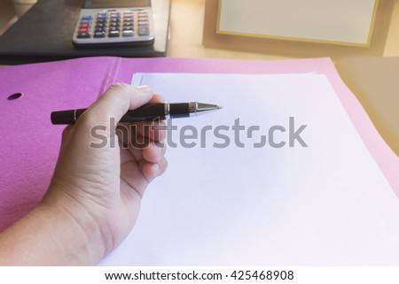 Hand with pen writing down on blank or empty white document paper on file folder in dim light office room