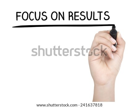 Hand with pen writing FOCUS ON RESULTS on whiteboard - stock photo